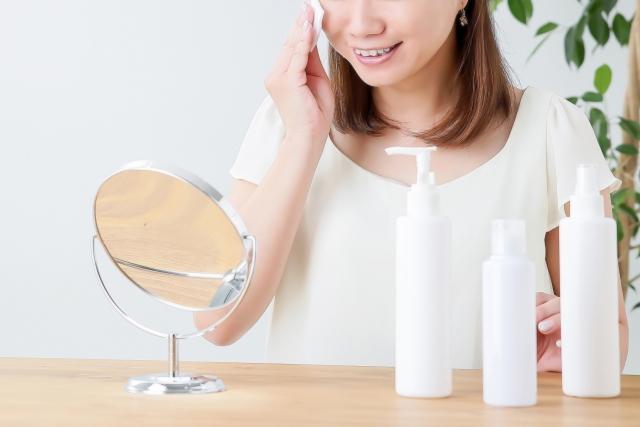 鏡の前で化粧水を試す女性