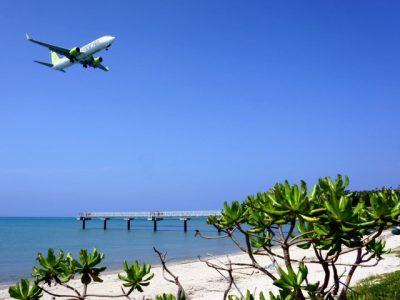 ビーチの晴れた空で飛んでいる飛行機