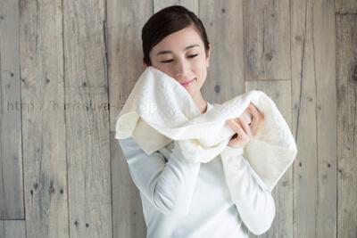 タオルを顔にあてて微笑む女性の画像