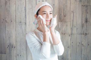 ヘアバンドを付けて洗顔泡を頬につける女性