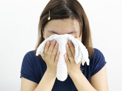 蒸しタオルで顔をふく女性