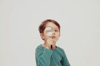 虫眼鏡を覗く少年