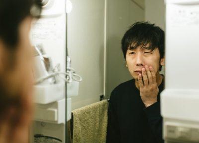 鏡をみて悩む男性