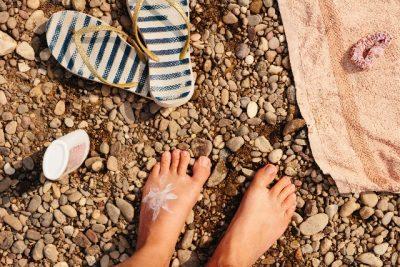 ビーチに素足と日焼け止めの写真