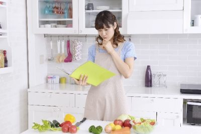キッチンで今日の献立に悩む女性の画像