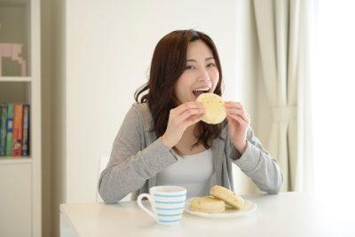 笑顔でおいしそうにパンを食べる女性の画像