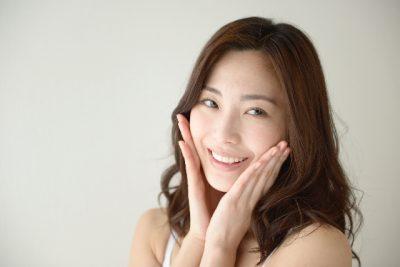 女性が微笑みながら頬に両手を当てている画像