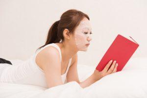 女性がシートマスクを付けてベッドで本を読んでいる画像