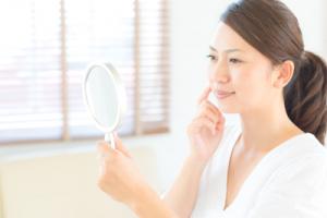 女性が鏡を見て微笑んでいる画像