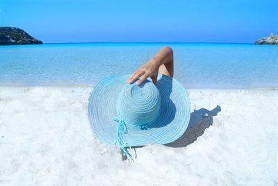 砂浜で寝転がり帽子をおさえている女性