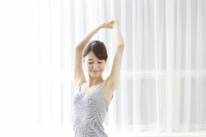 キャミソール着て両手を高く上げ伸びをする女性