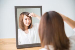 鏡を見ておでこを気にする女性