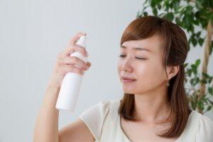 顔に化粧品を吹きかける女性