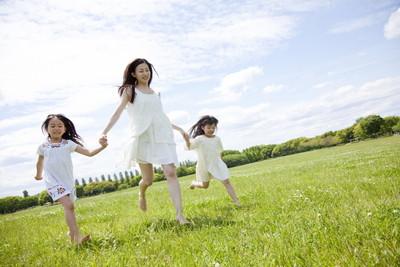 スキップしている女性と子供2人