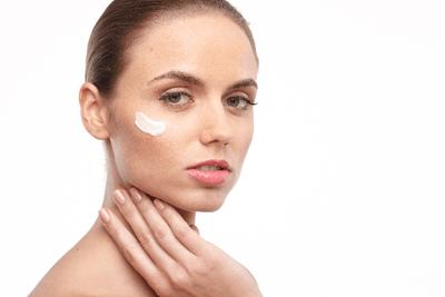 化粧品クリームを顔に塗った女性のイメージ写真