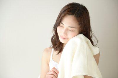 タオルで顔を拭く女性の画像
