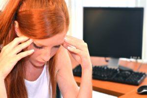 パソコンの前で辛い表情をする外国人女性