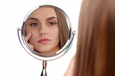 鏡をのぞきこむ外国人女性
