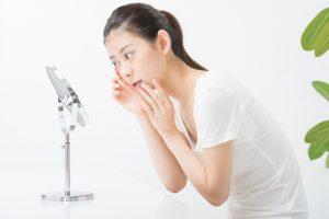 鏡で肌をチェックする女性
