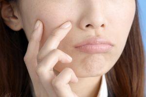 指で口の周りを触る女性のアップ