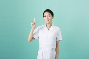 指を立てている笑顔の看護師女性