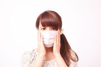 マスクをして両頬を抑える女性