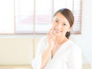 頬に指を当てる女性の画像