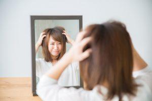鏡の前で悩む女性