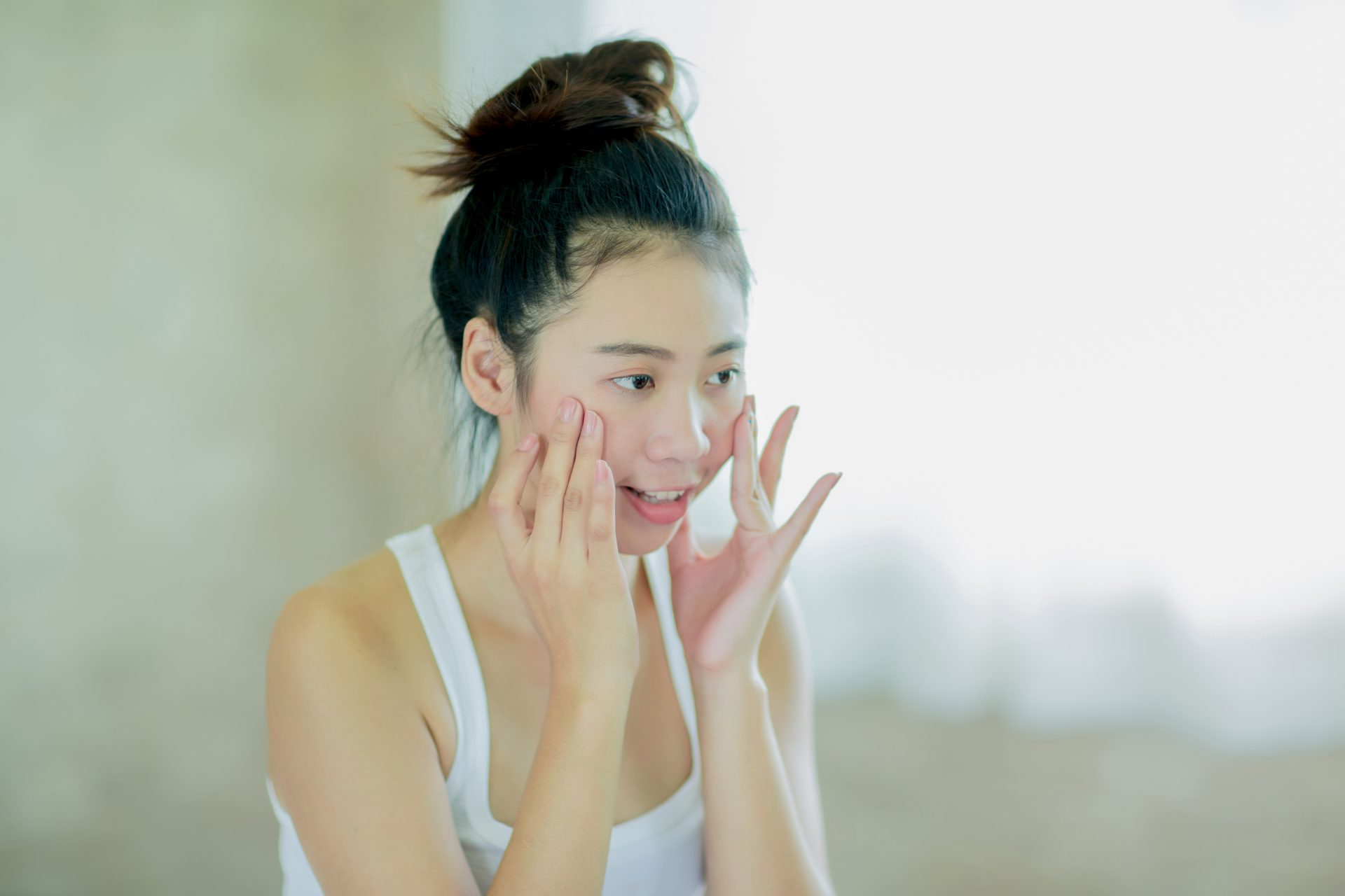 手に頬をあて、鏡を見る女性