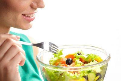女性がサラダを食べている画像