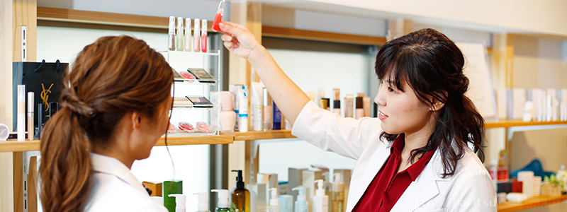 化粧品を手に取る名嘉山