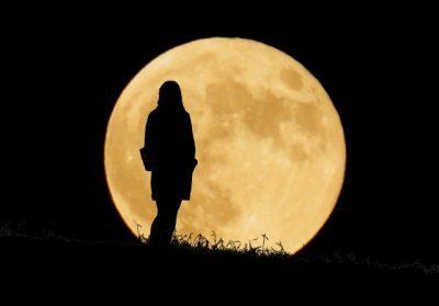 月を背景に女性がたたずんでいる