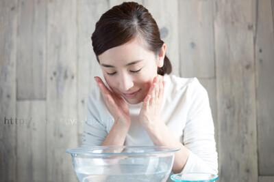 桶の水で頬をすすぐ女性