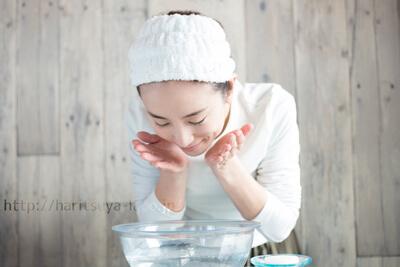 ヘアバンドを付けて水で頬をすすぐ女性