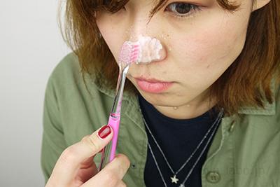 鼻に重曹ペーストをつけて歯ブラシでこすっている