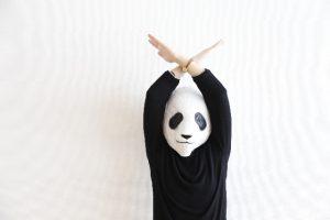 パンダの覆面をかぶった人がバツポーズをしている画像