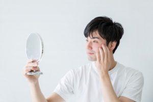 鏡を見て肌を気にする男性