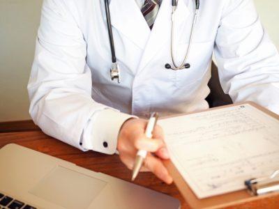 医者がカルテを持って診察している画像