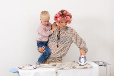 ヘアセットしながら子どもを抱いてアイロンをかける女性