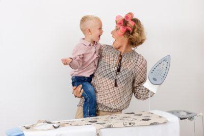 子供を抱えてアイロンをする忙しい女性