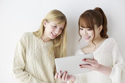 女性ふたりがタブレットを見て笑っている画像