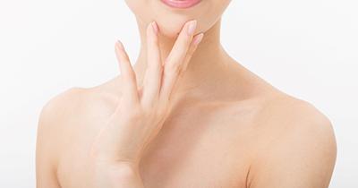 女性が顎に手を当てて微笑んでいる画像