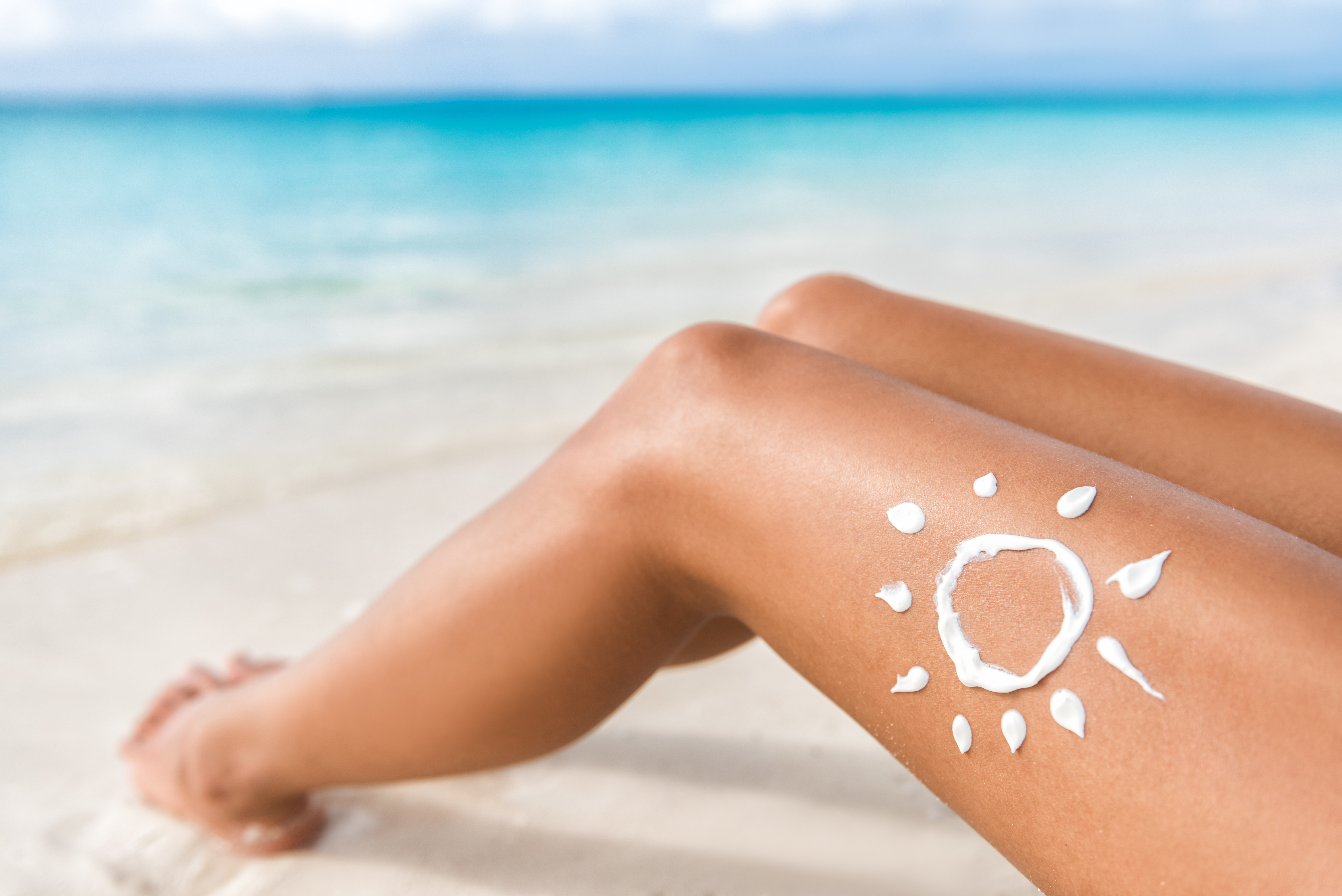 足に日焼け止めを塗る