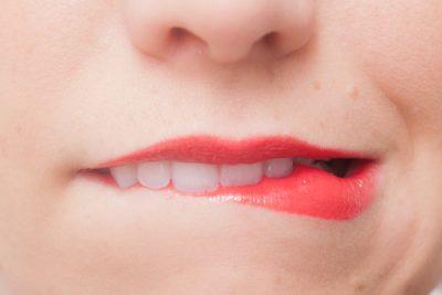 口紅をつけた女性が唇をかんでいる