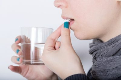 右手にグラス左手でサプリメント飲む女性