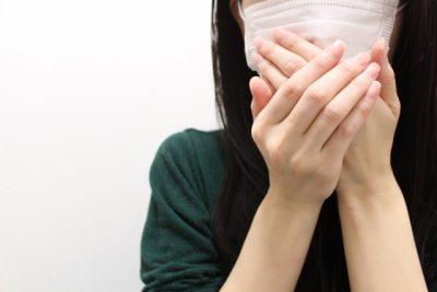 マスクをした口元を両手で隠す女性のアップ