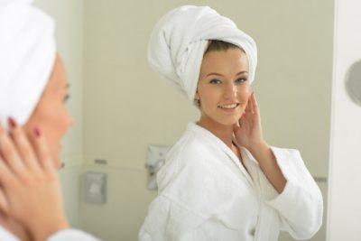 女性がバスルームの鏡を見て微笑んでいる