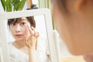 鏡を見ながらメイクする女性