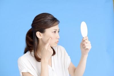 鏡を見て肌を気にする女性