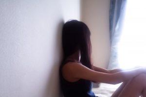 窓から空を見上げる女性の画像